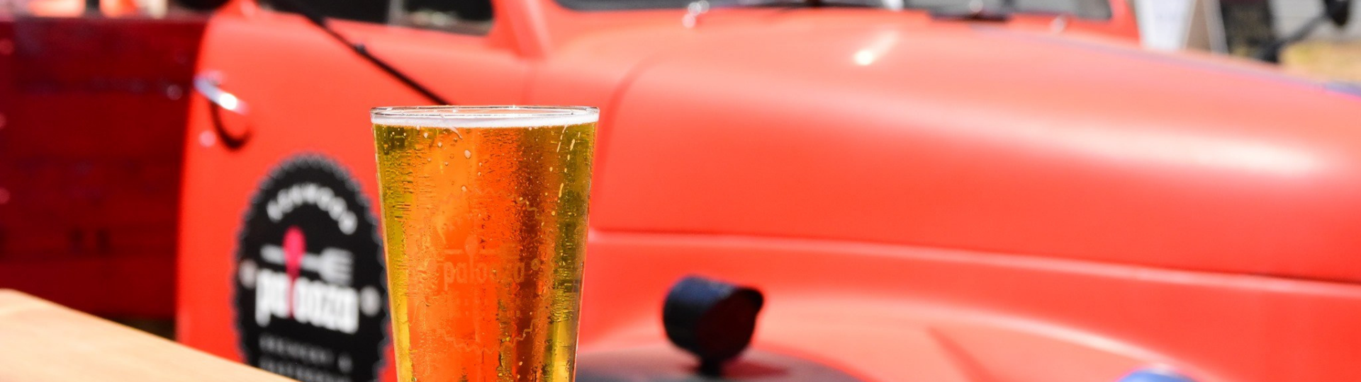 glass of beer on table, red classic pick up truck in background