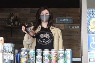 woman wearing face mask serving beer